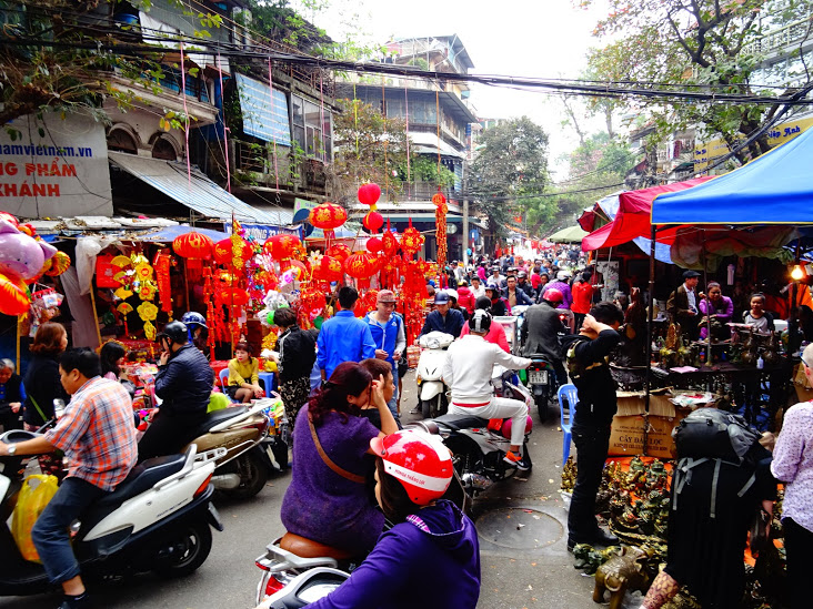 A busy market street in Hanoi filled with mopeds