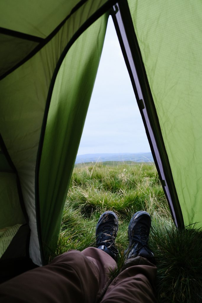Legs coming out of tent with mountain view