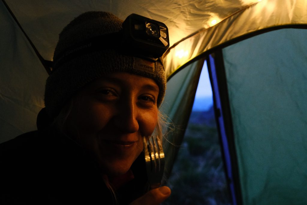 Girl with a headtorch eating a camping meal in tent