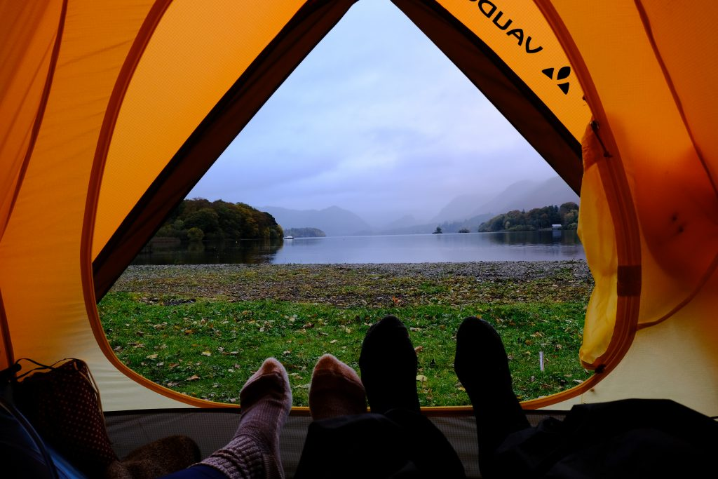 Couple camping in a tent with lake view