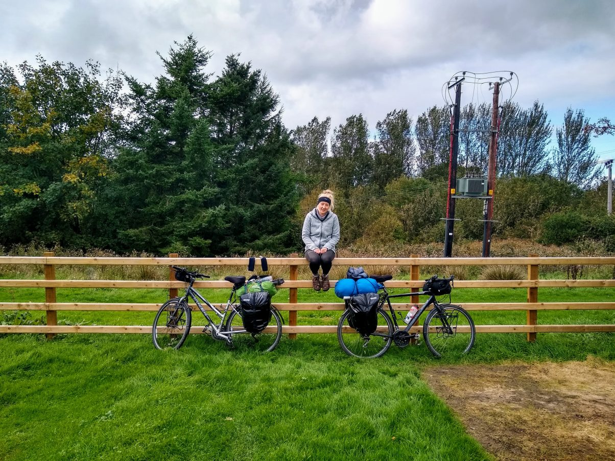 Cycle tour girl sitting with bikes on fence