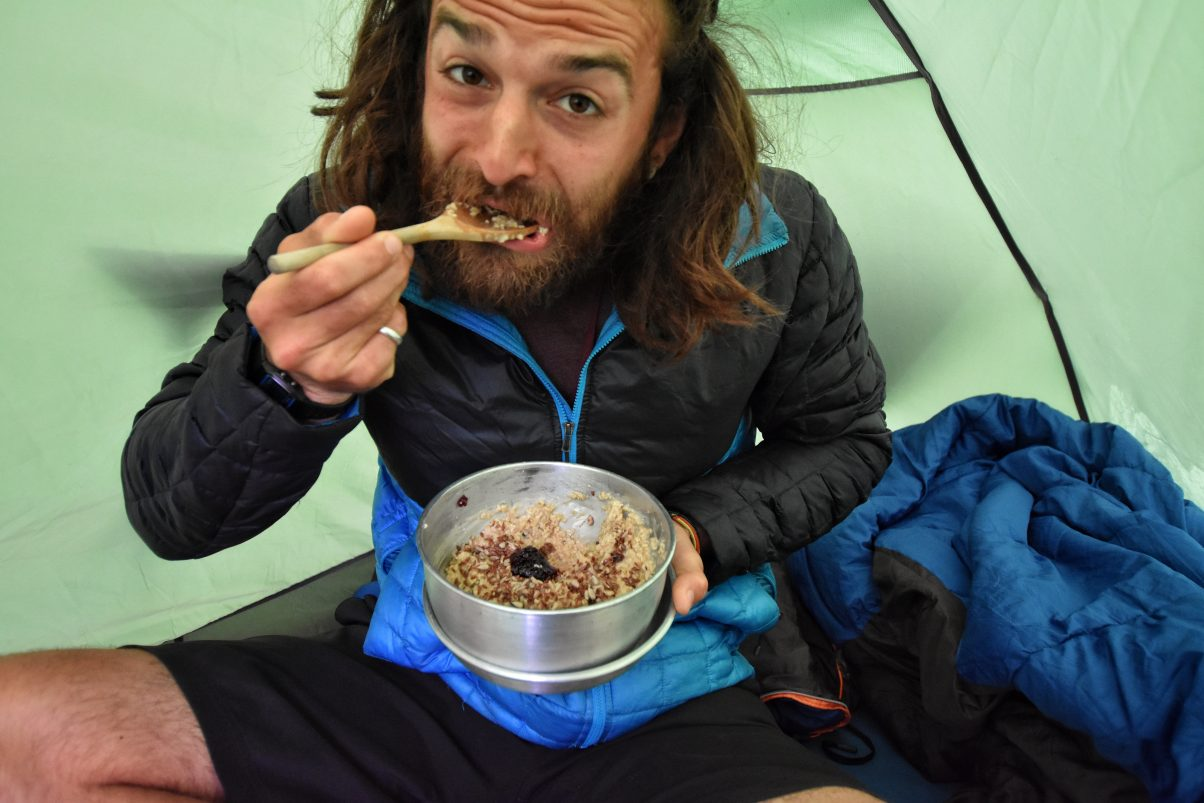 Man eating porridge in tent in France