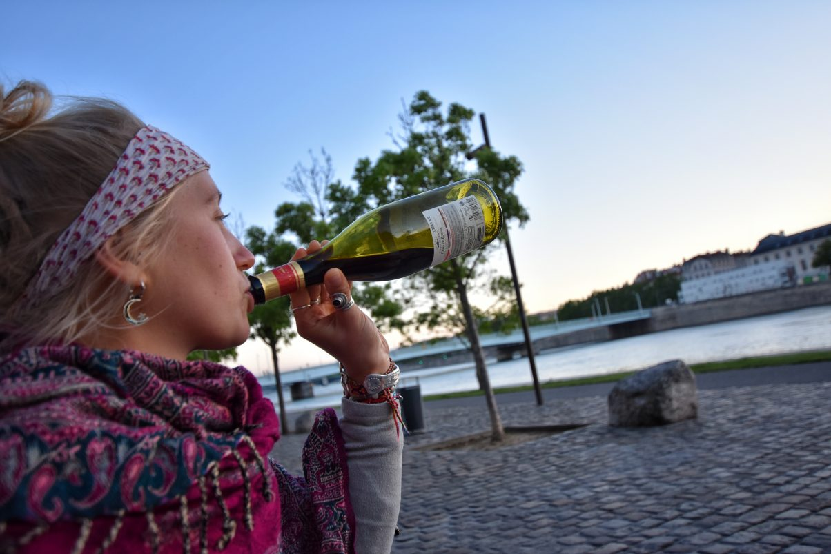 Girl drinking bottle of wine in Lyon by river