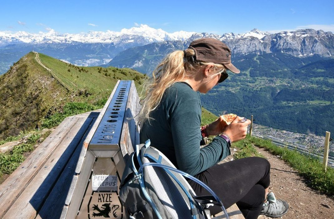 Girl on mountain eating vegan hiking food