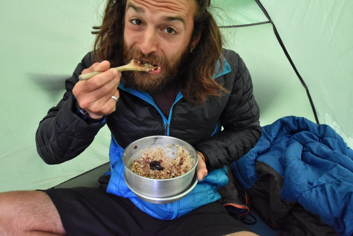 Man eating breakfast from pan in tent