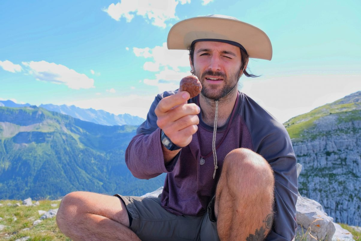 Man eating vegan energy balls on hiking trail