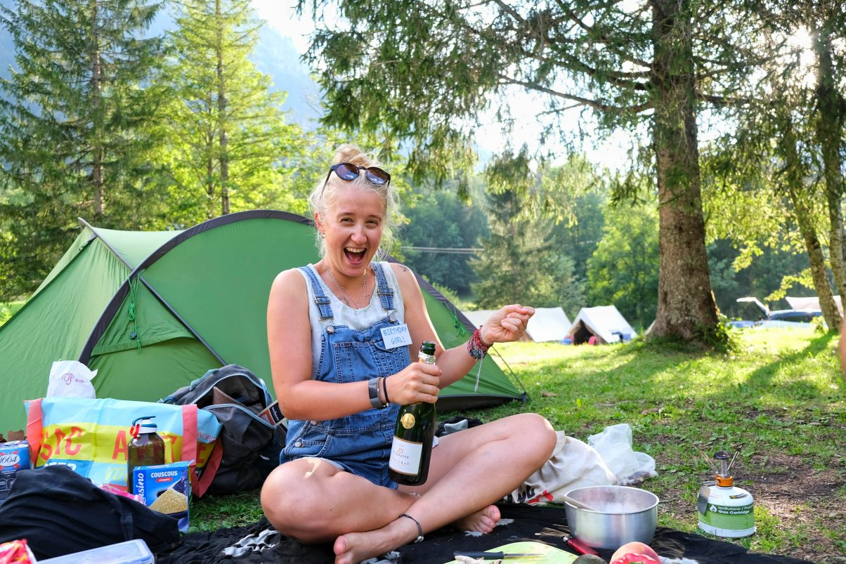 Girl popping champagne in the forest