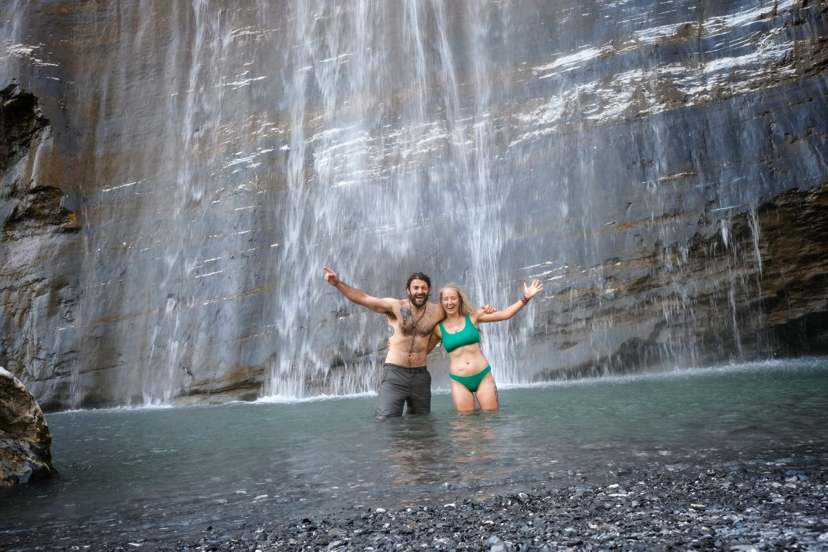 Couple swimming in waterfall