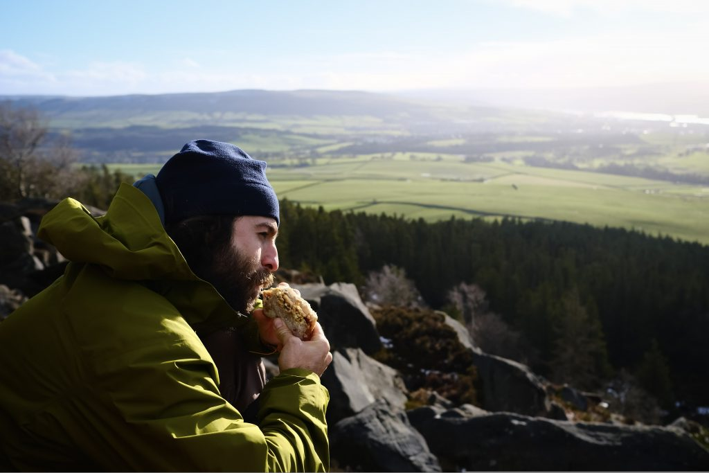 Man eating a hiking lunch on mountainside
