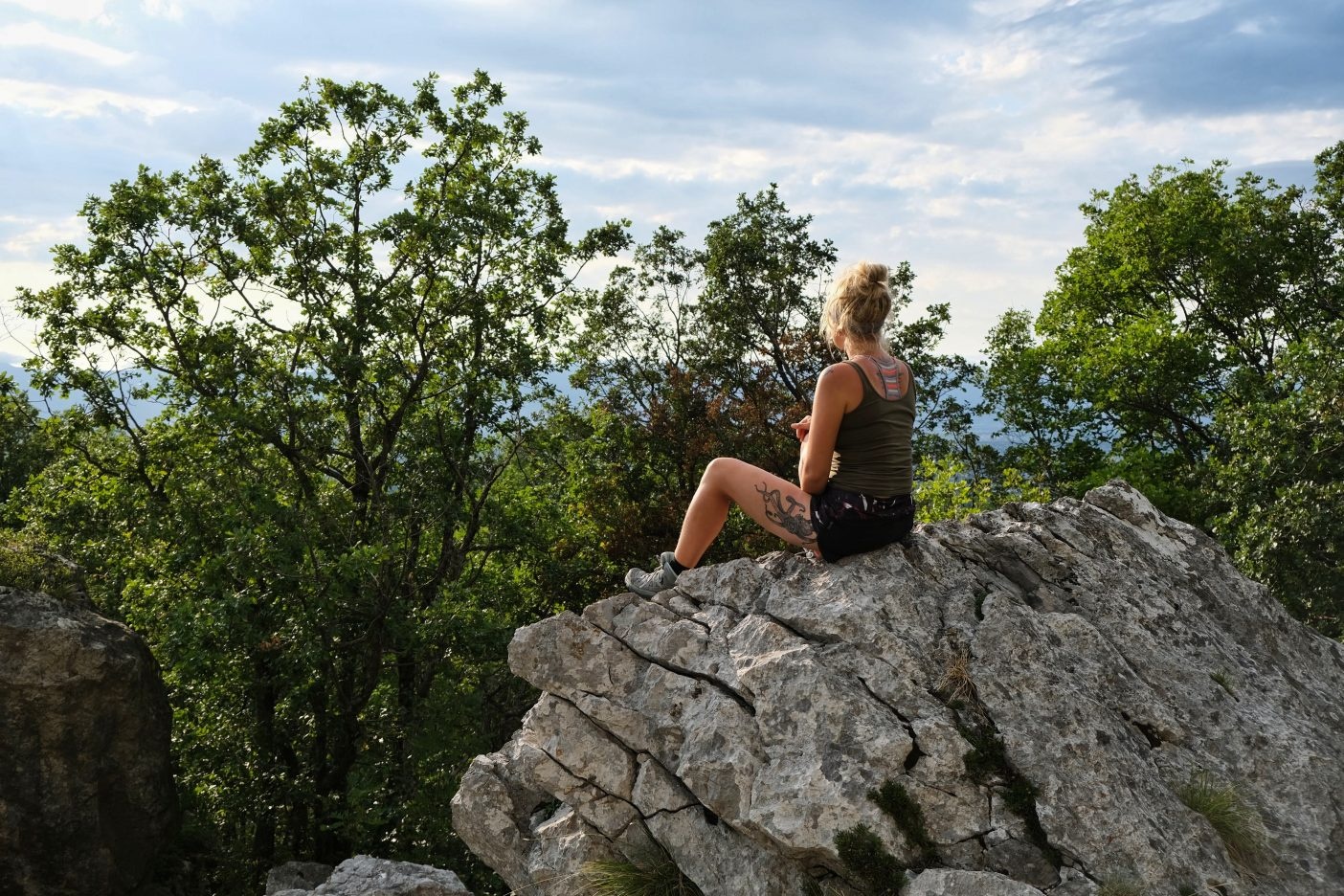 Girl in the mountains on hiking trip sitting in nature
