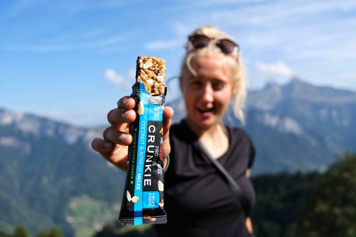 Girl in mountains holding vegan protein bar