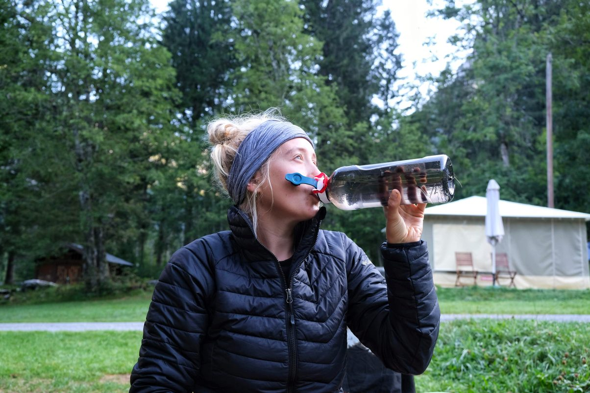 Sustainable hiking girl drinking from water bottle