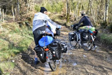 Man and woman pushing touring bikes in the outdoors