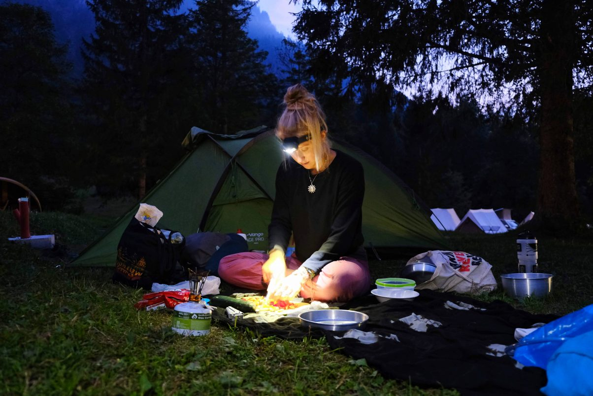 Girl using a Black Diamond headtorch to cook on camping fire