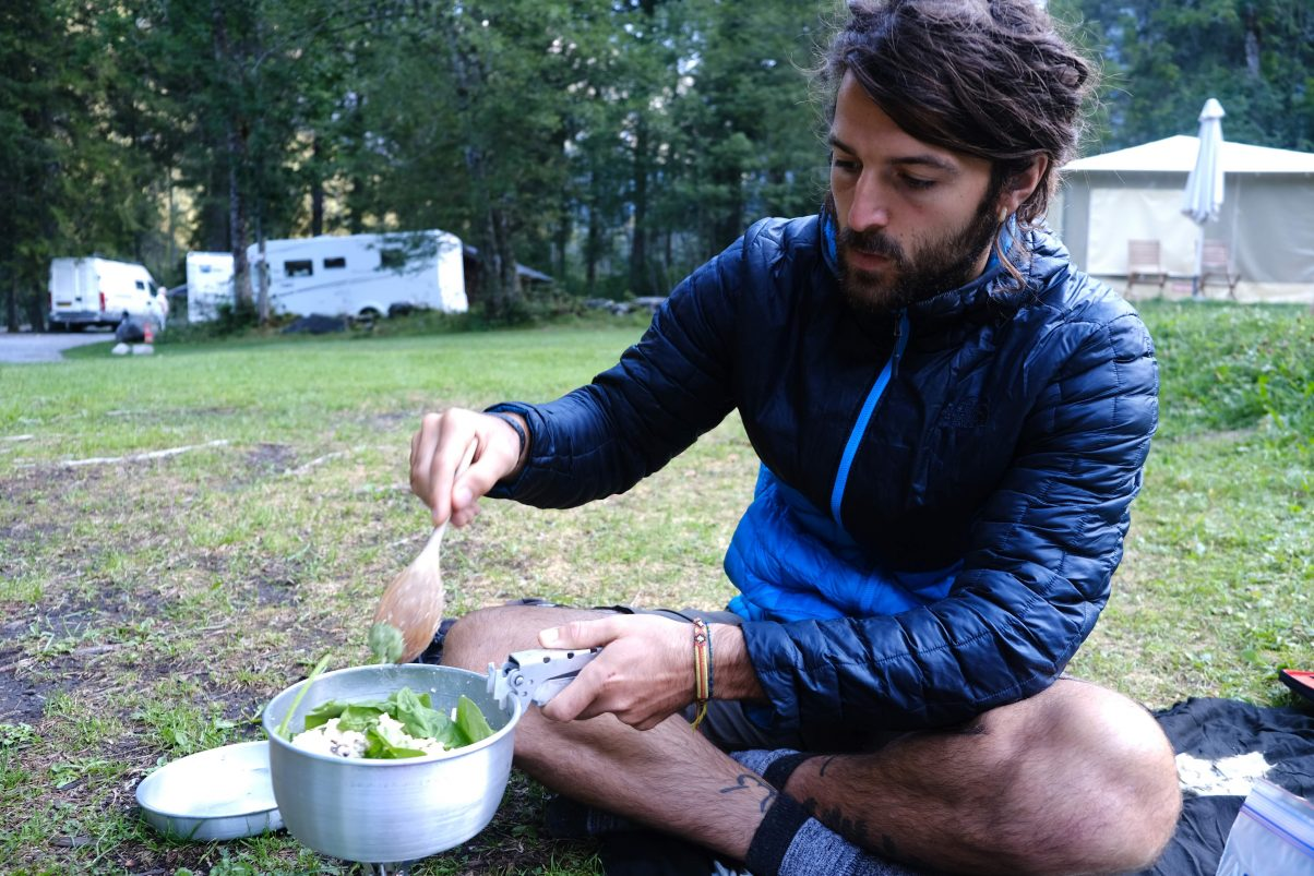 Man cooking on a camp stove with a North face synthetic insulated jacket