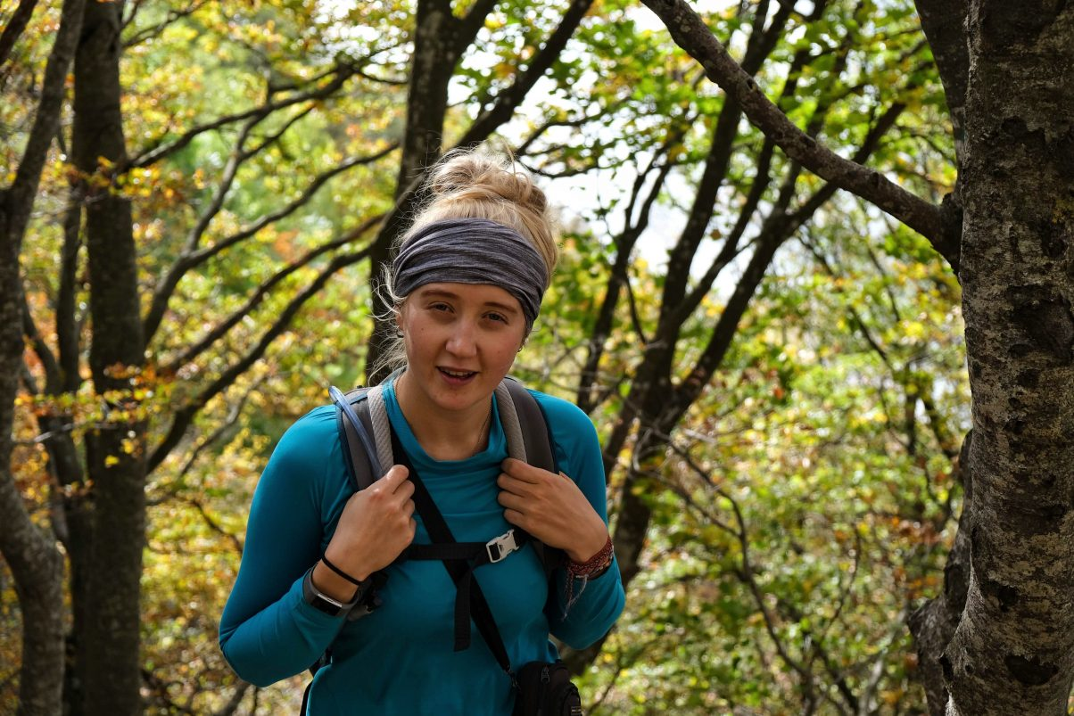 Girl hiking through forest wearing a buff