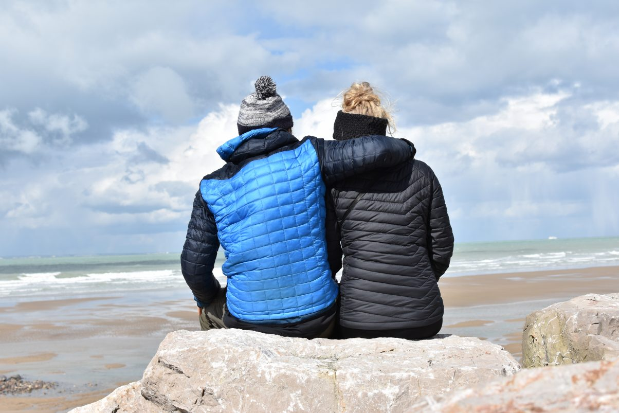 Couple sitting on the coast in insulated jackets