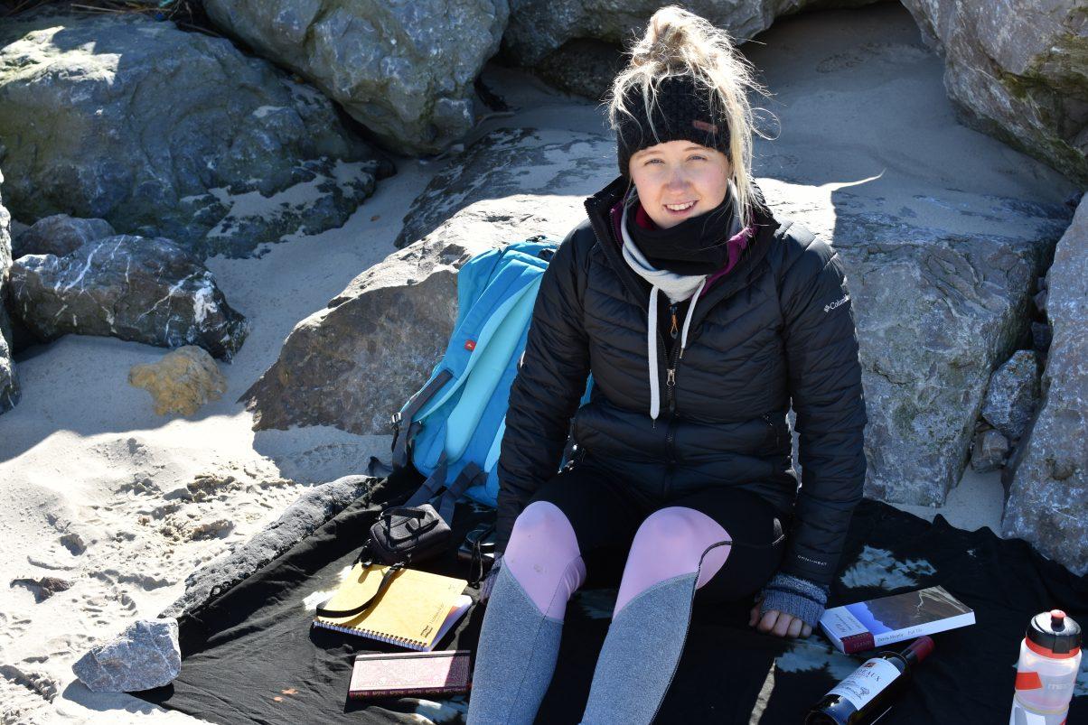 Vegan girl sitting on beach in coat
