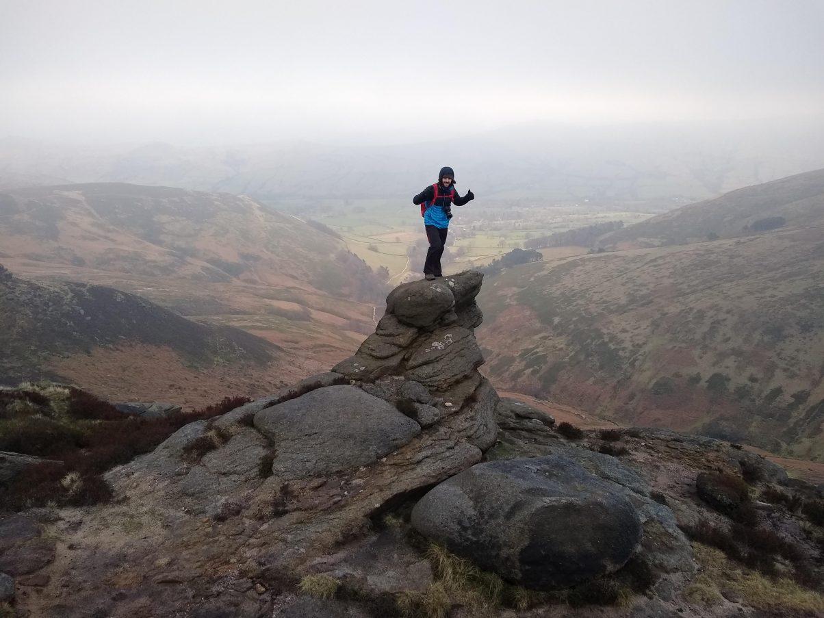 Man climbing peak in the Peak District UK