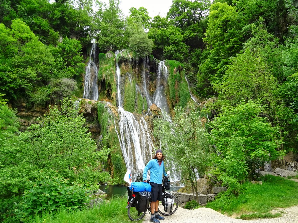 Male cycle tourer in front of waterfall