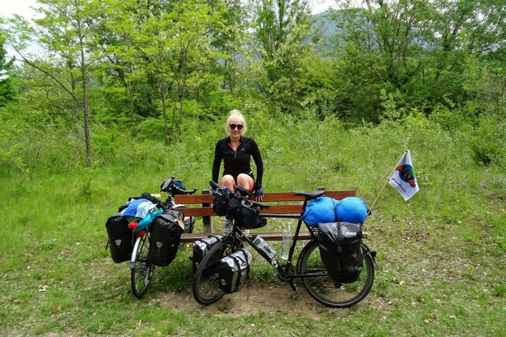 Female cycle touring sitting with bike