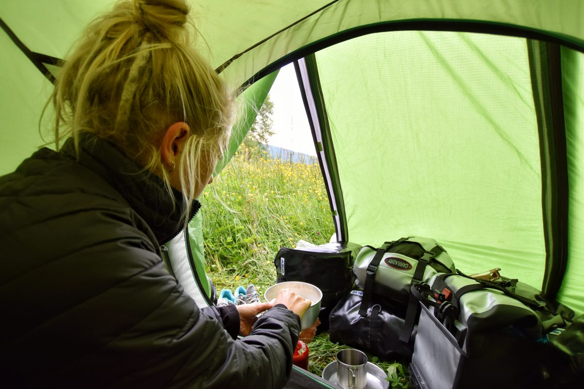 Girl cooking in tent with panniers in view