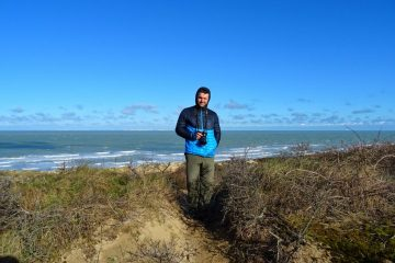 Man hiking in synthetic insulated jacket on the beach