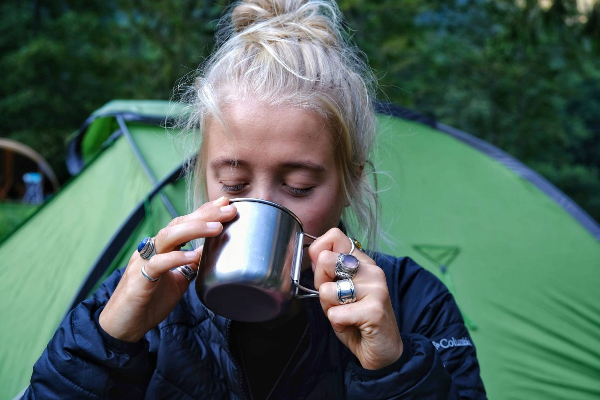 Eco camper sipping from mug