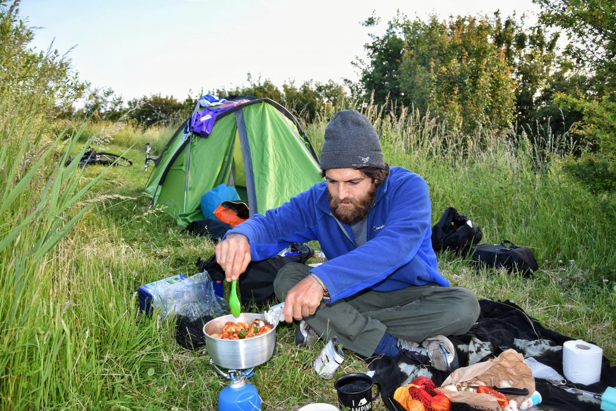 Man cooking with camping equipment