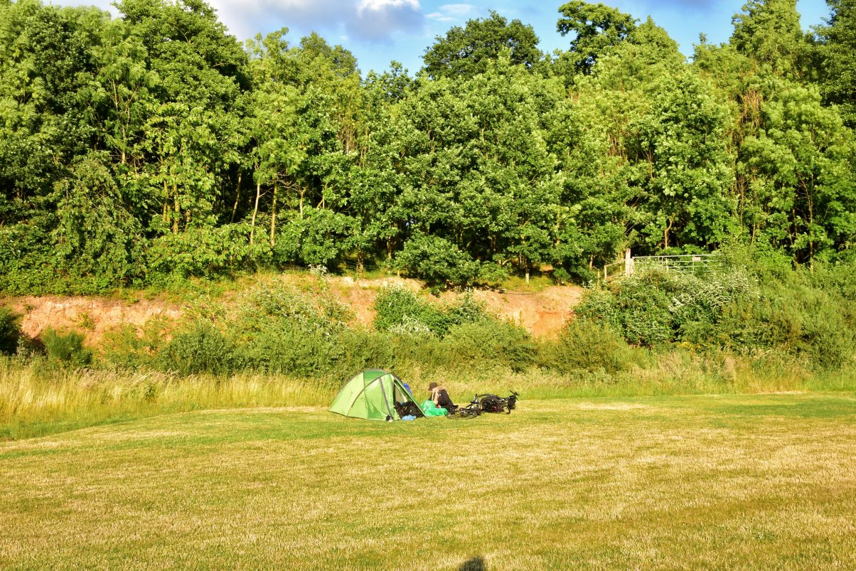 Camping gear and tent in field