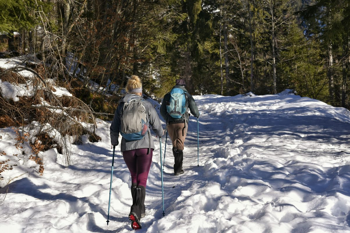 People hiking during winter along mountain path