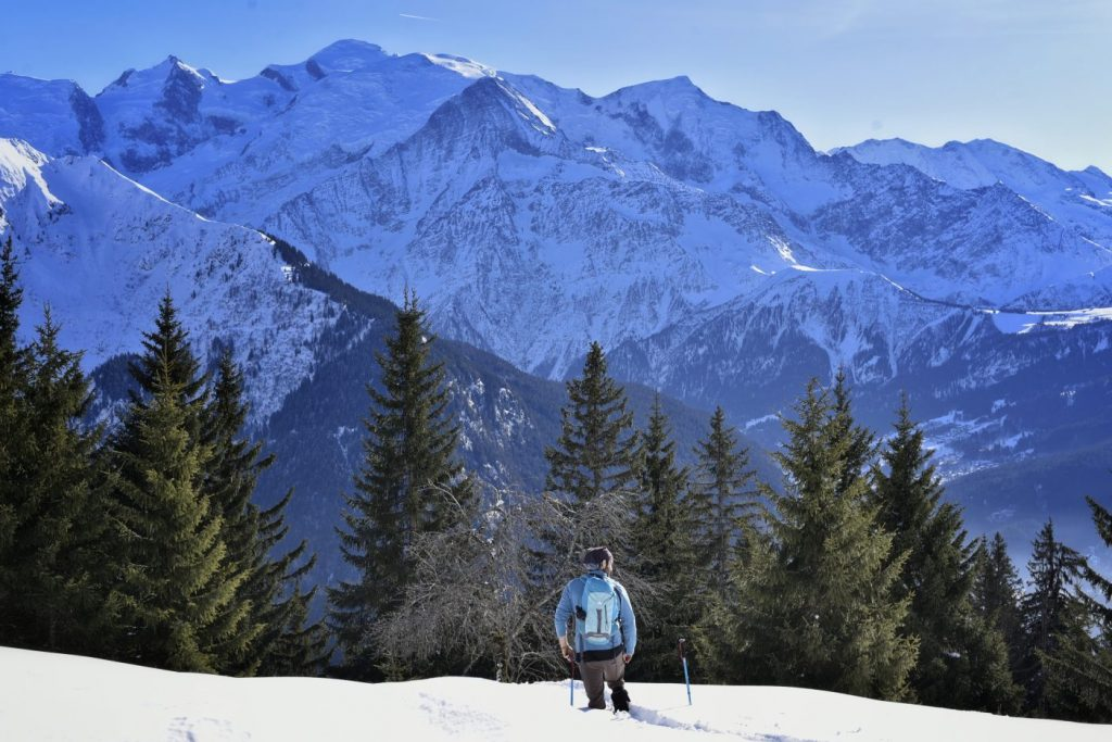 Man hiking through snow in French Alps in front of Mont Blanc Mountain