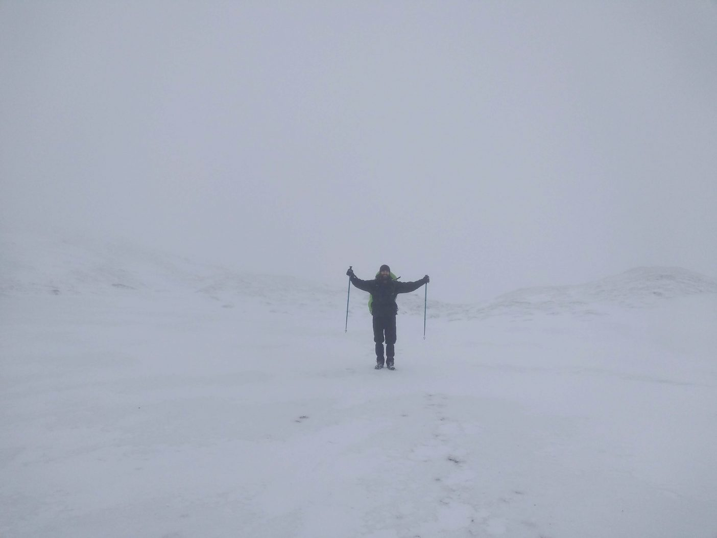 Man hiking in snow in whiteout