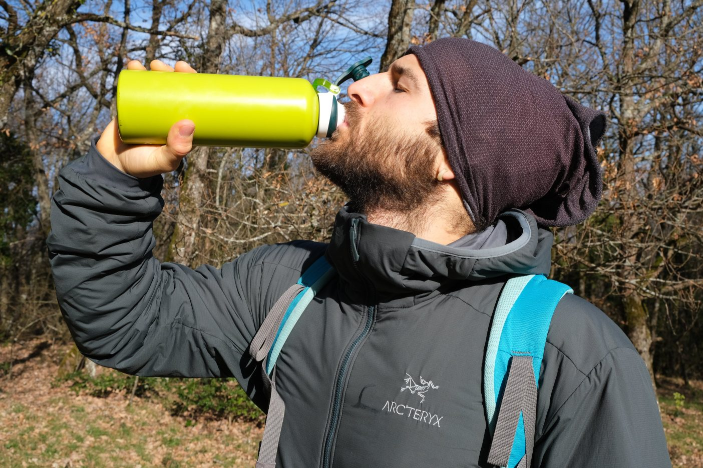 Man drinking from flask in Arc'teryx insulated hoody