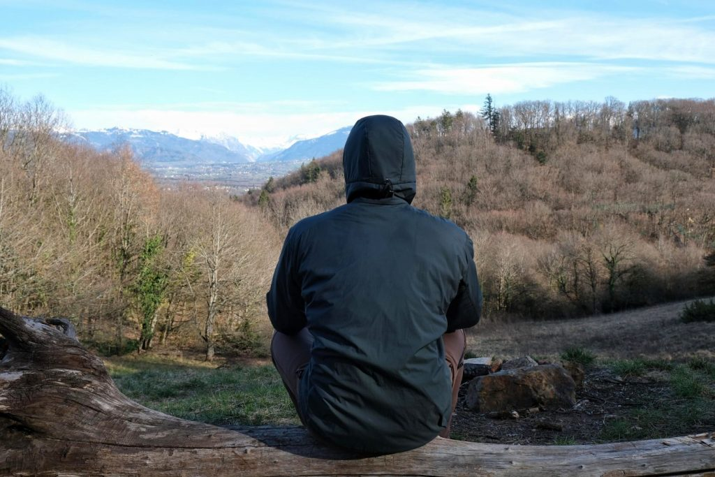 Man sitting in woods wearing Arc'teryx LT jacket