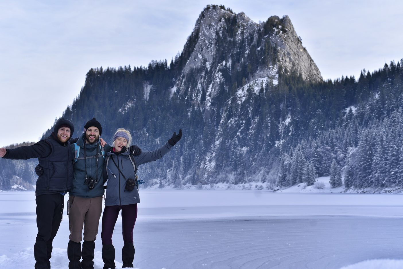 Three people in front of winter mountains