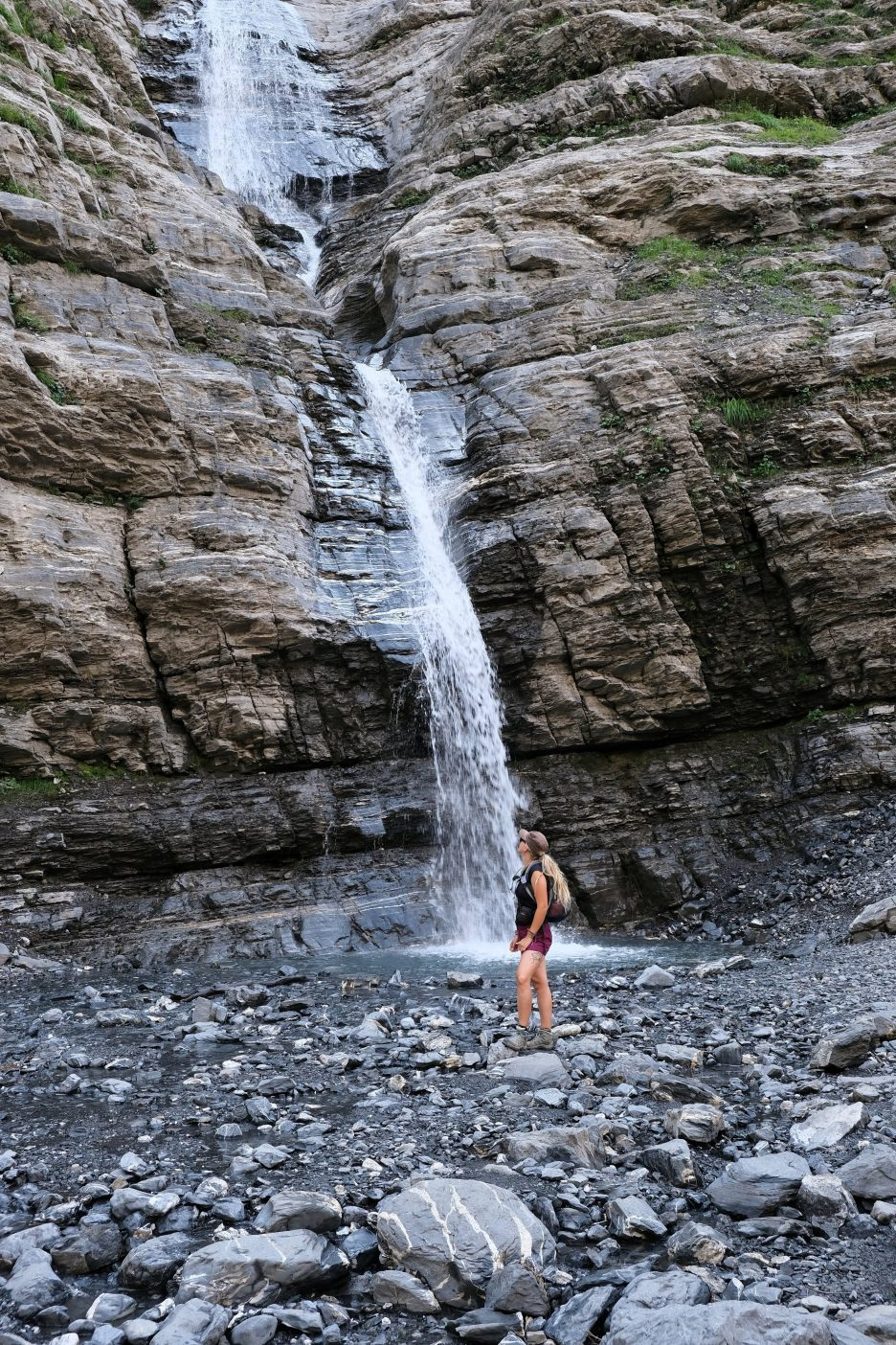 Girl standing next to waterfall