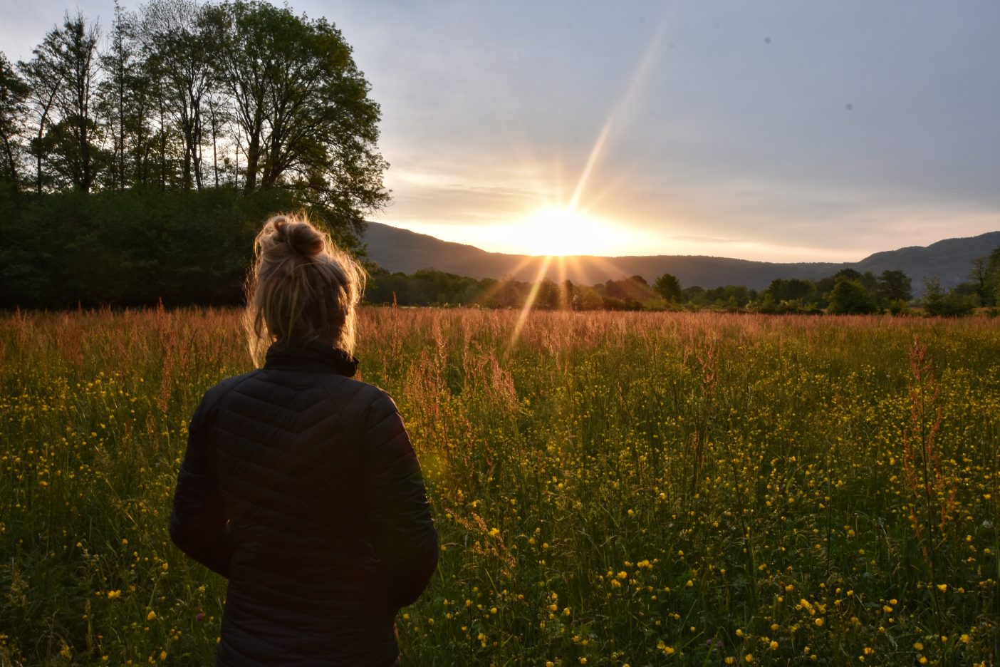 Girl watching sunrise in buttercup field