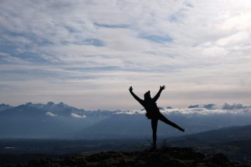 Silhouette of girl on top of moutain