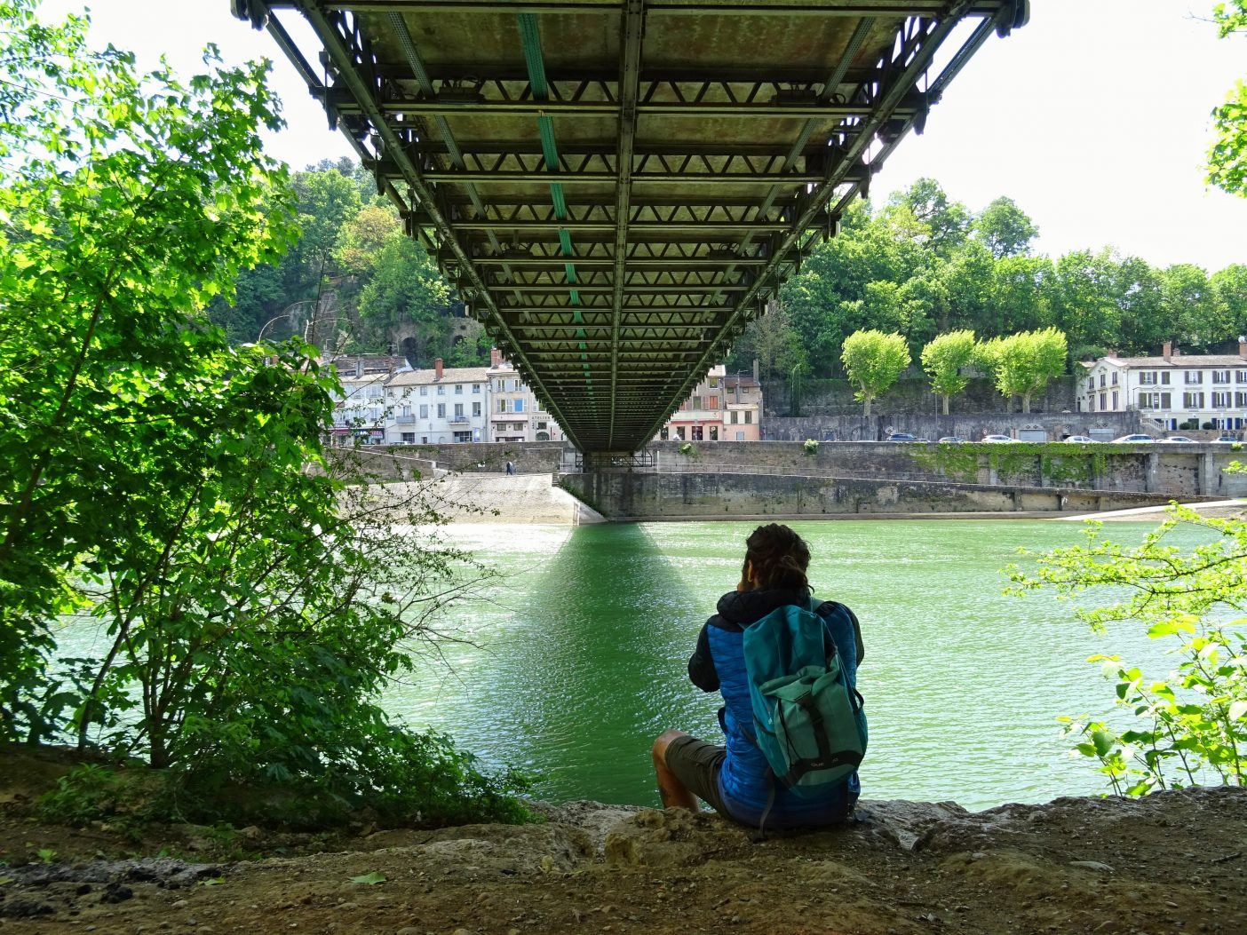 Man sitting under bridge taking photo