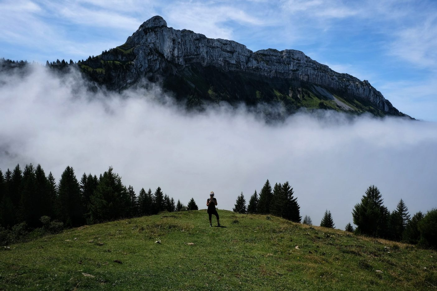 Girl on peak with clouds around