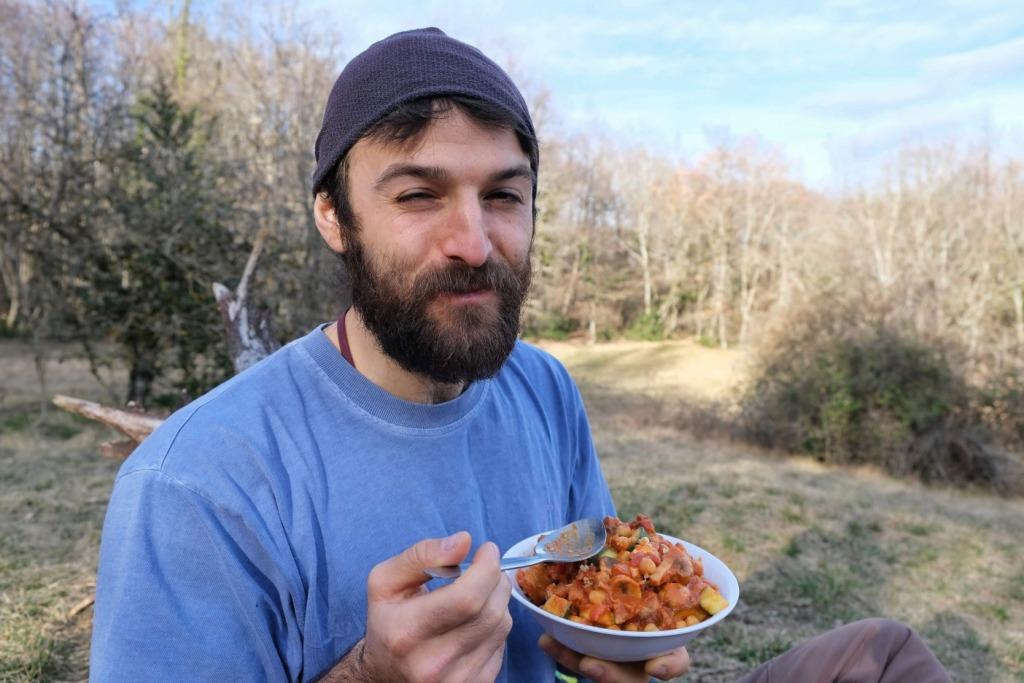 Man eating vegan campfire food