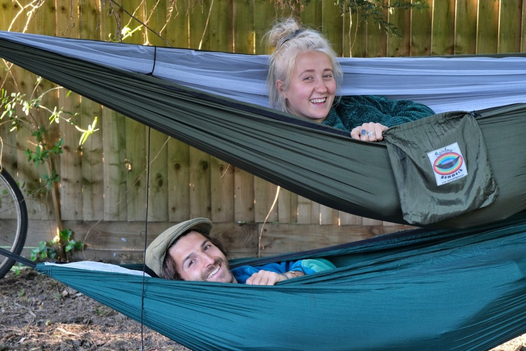 A couple camping in a hammock