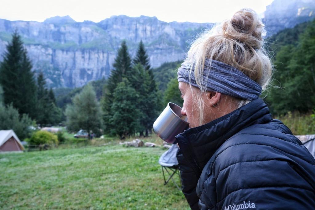 Girl camping and drinking from tin mug