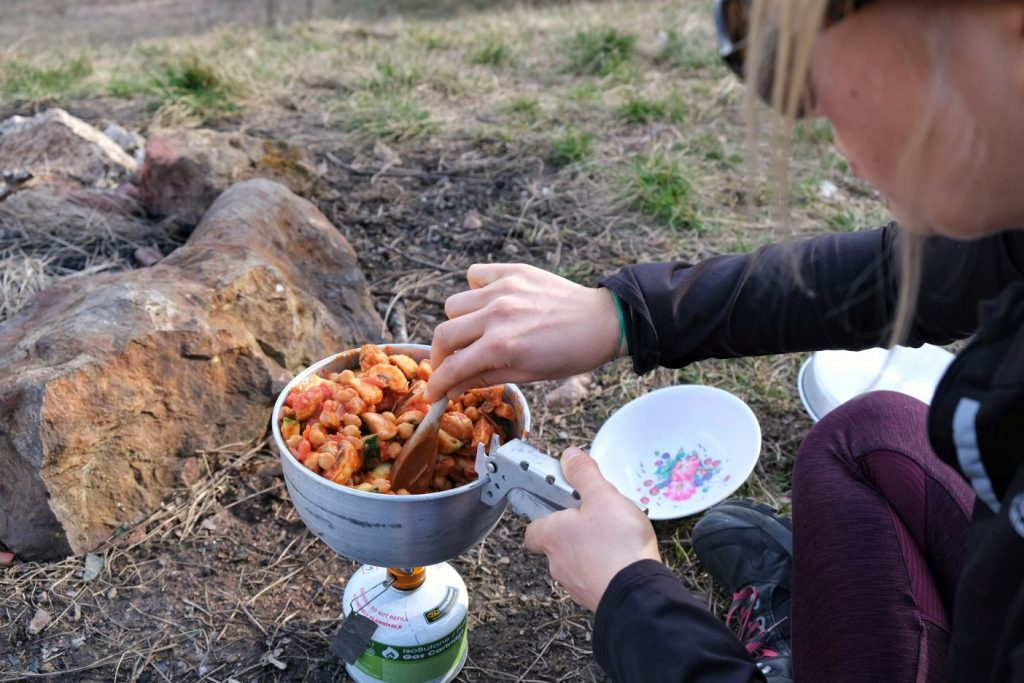 Girl stirring vegan peanut butter curry on camp stove
