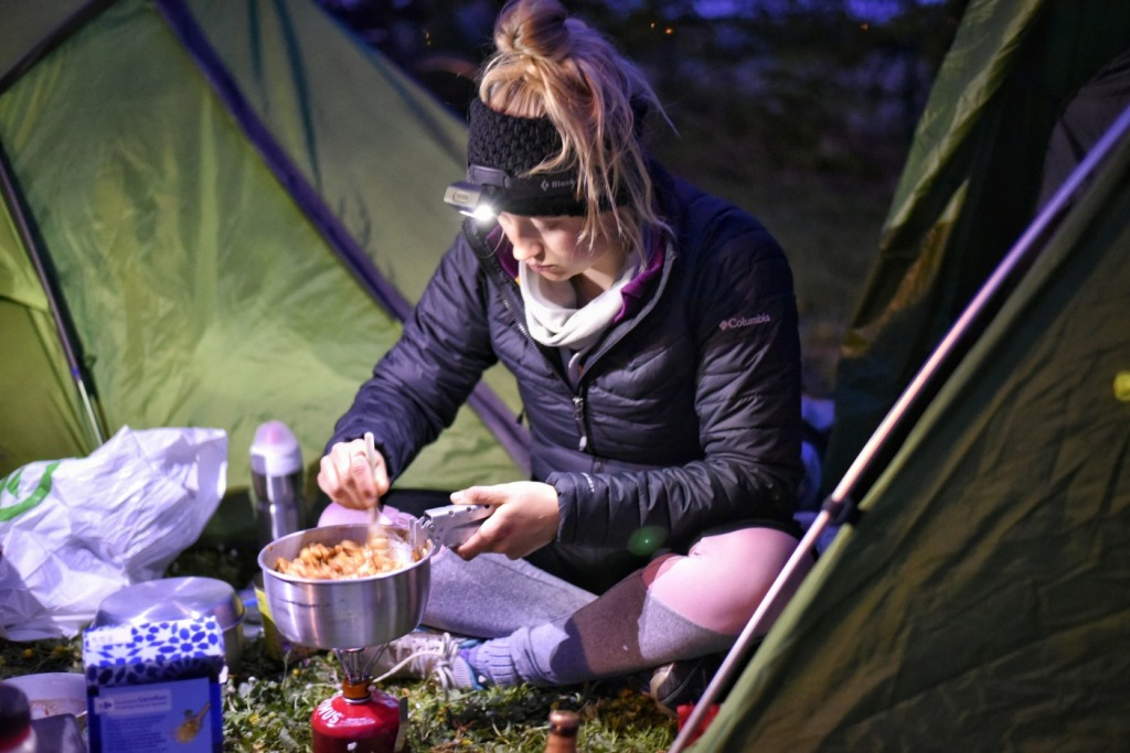 Girl cooking a campstove meal with a headtorch on