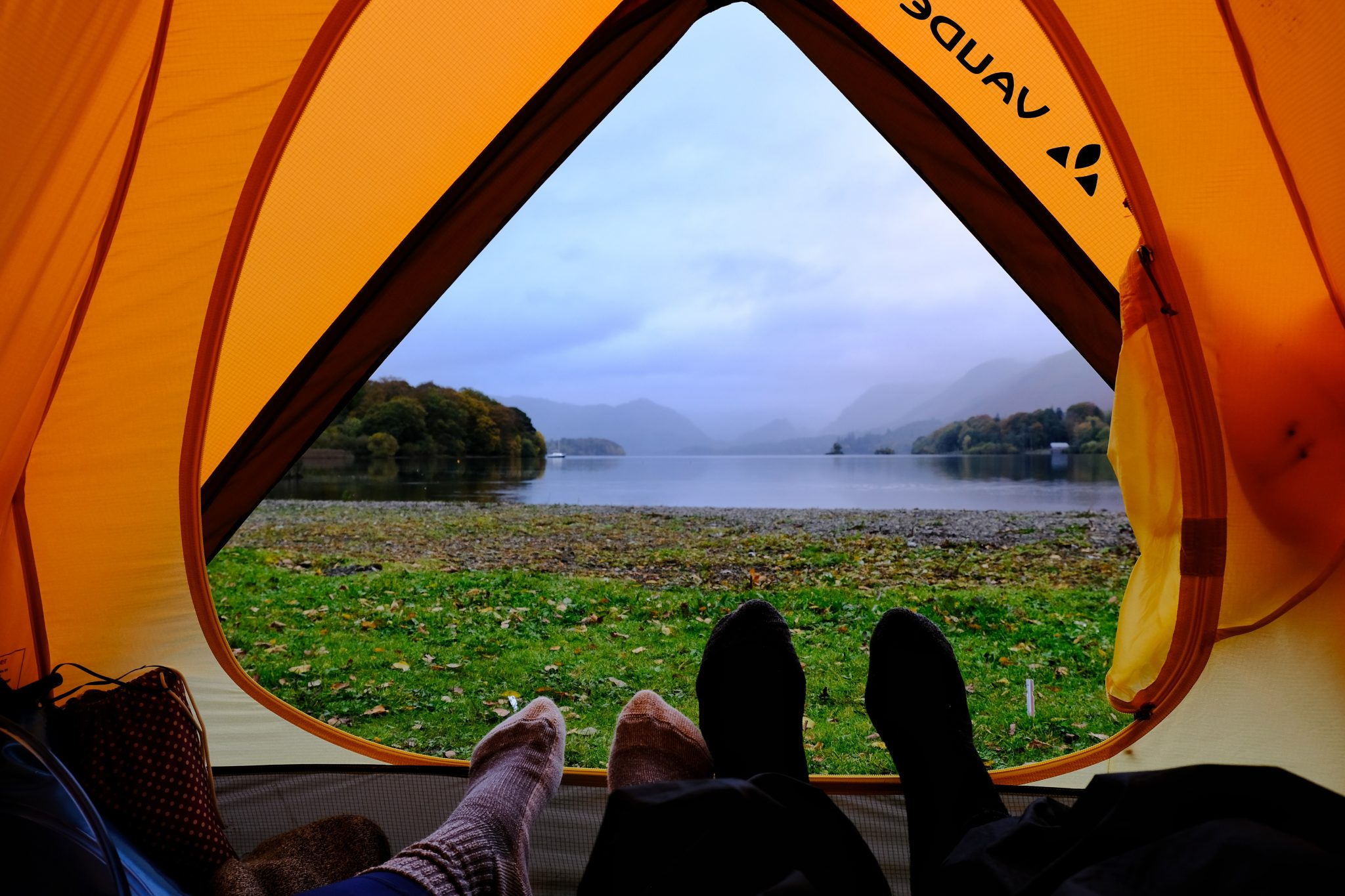 Couple camping in a tent overlooking a lake