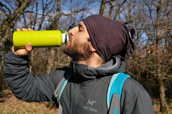 Man drinking from reusable water bottle