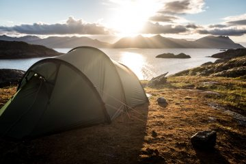 Camping in front of lake in a two person cycle touring tent
