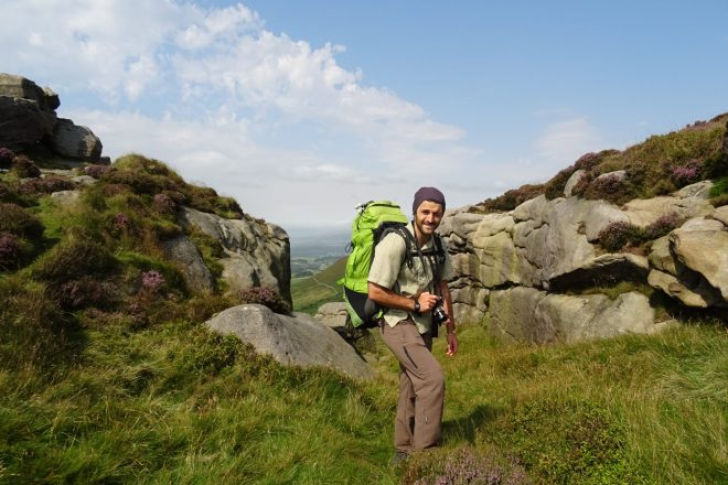 Man backpacking with rucksack along a UK hiking trail